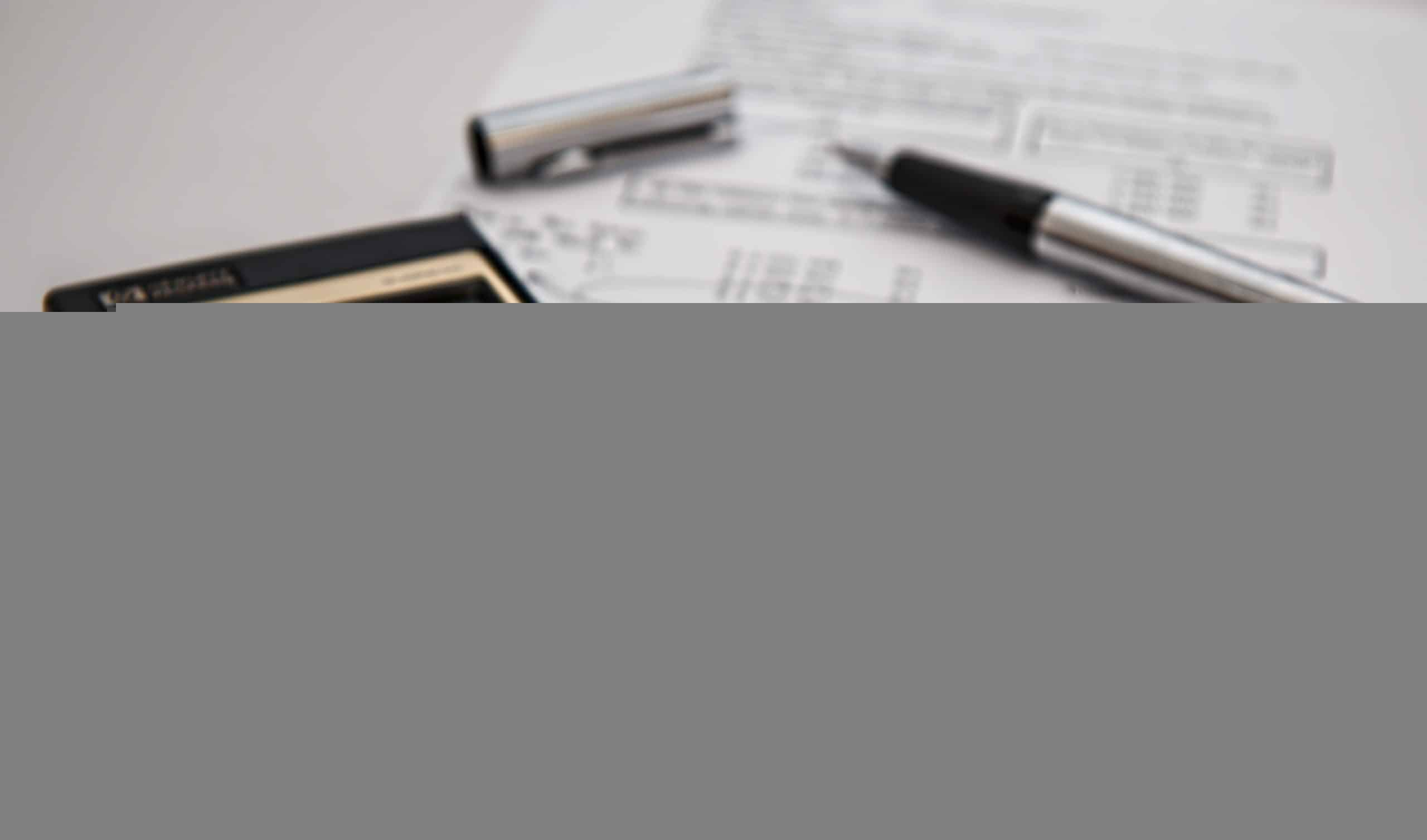 photo of finance sheet with a pen and calculator